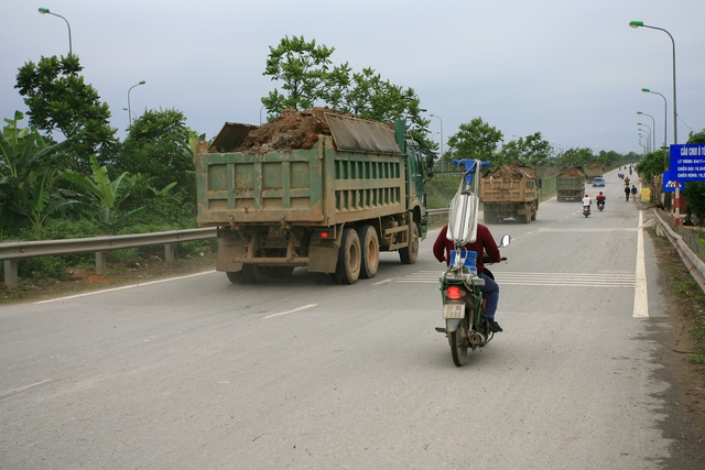 Cả đoàn xe tải chở đất vượt quá thành xe chạy rầm rầm trên Đại lộ Thăng Long.