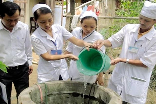 Cán bộ y tế hướng dẫn người dân xử lý nước sinh hoạt trong mùa mưa lũ. Ảnh: V.Vũ