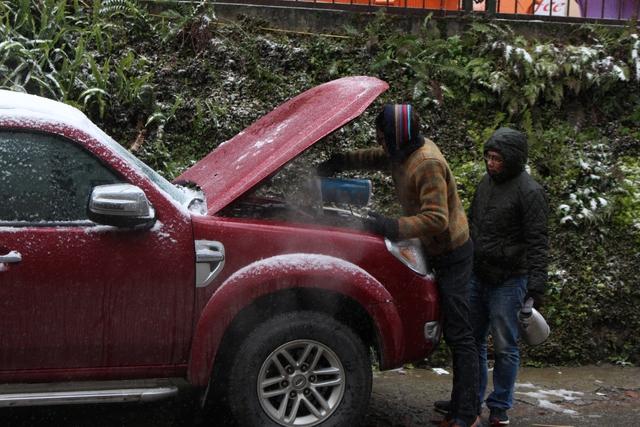 Người dân địa phương sử dụng nước nóng để làm ấm động cơ ô tô. Ảnh: Nghiêm Linh.