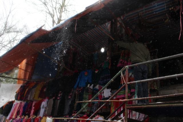 Người dân địa phương đang cố g đi lớp tuyết dầy che phủ trên mái nhà. Ảnh: Nghiêm Linh.