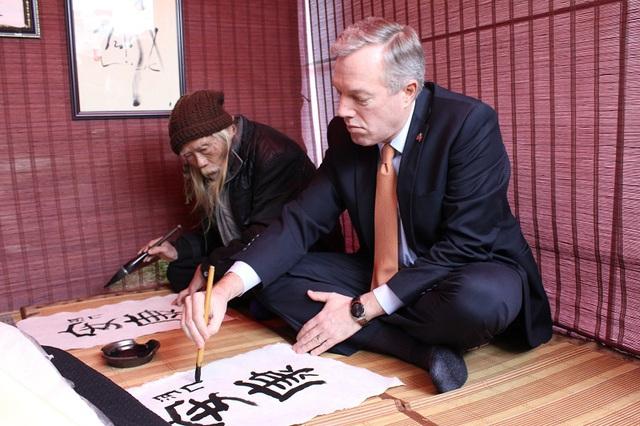 Trong lần đến thăm này, Đại sứ Ted Osius đã được TS Cung Khắc Lược dạy viết chữ An Khang.