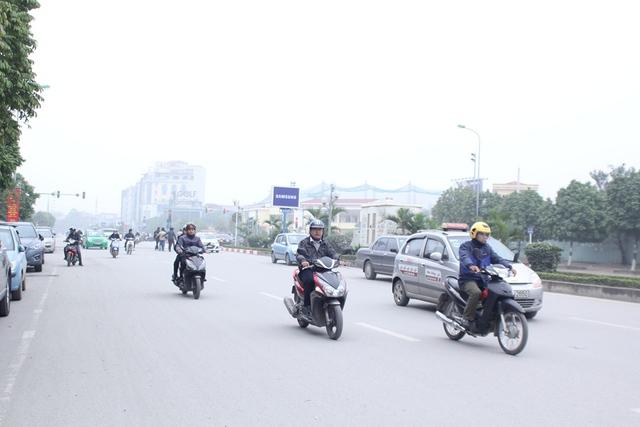 Một góc đường Dương Đình Nghệ bị hạn chế tầm nhìn vì sương mù. Nhiều phương tiện phải bật đèn để tiện di chuyển. Ảnh: Đình Việt.