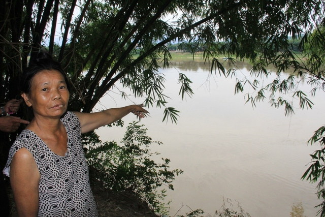 Bà Trần Thị Bảy đứng ở sân nhà chỉ xuống bờ sông sạt lở cách vài bước chân. Ảnh: Đức Hoàng