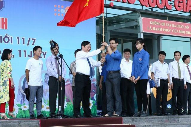 Thay mặt lãnh đạo Bộ Y tế, Thứ trưởng Nguyễn Viết Tiến trao cờ cho đại diện đoàn thanh niên trong buổi lễ diễu hành cổ động hưởng ứng Ngày Dân số Thế giới. Ảnh Chí Cường