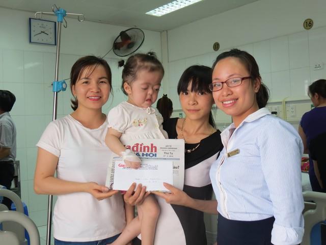 PV Phương Thuận đại diện chuyên mục Vòng tay nhân ái (bên trái) cùng đại diện cán bộ phòng công tác xã hội BV Việt Đức trao tiền bạn đọc hảo tâm ủng hộ qua Báo cho cháu Quỳnh Anh. Ảnh Tất Thắng