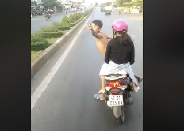 Nam thanh niên cởi trần, không đội mũ bảo hiểm chở bạn gái lạng lách trước đầu xe khách