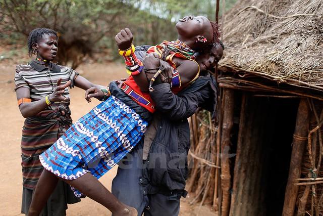 Một người đàn ông giữ cho cô bé không vùng vẫy khi cô cố chạy trốn. Ảnh: Siegfried Modola/Reuters