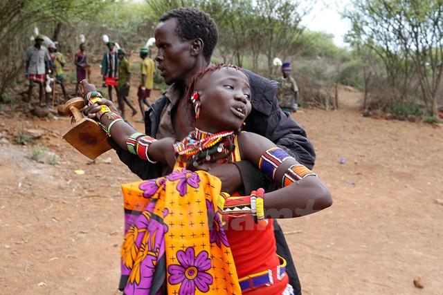 Người đàn ông lôi cô gái trả về nhà sau khi cô chạy trốn bất thành. Ảnh: Siegfried Modola/Reuters