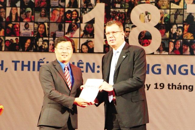 Ông Arthur Erken - Trưởng Đại diện UNFPA tại Việt Nam trao bản Báo cáo tình trạng dân số thế giới 2014 cho ông Lê Quốc Phong - Bí thư BCH Trung ương Đoàn, Chủ tịch Hội Sinh viên Việt Nam. ảnh: Chí Cường