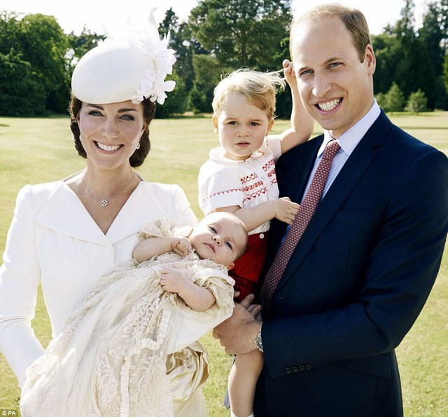 Prince George plays with his hair as the family of four pose for their first official snap together - one of four that the royal couple chose to release from the special day