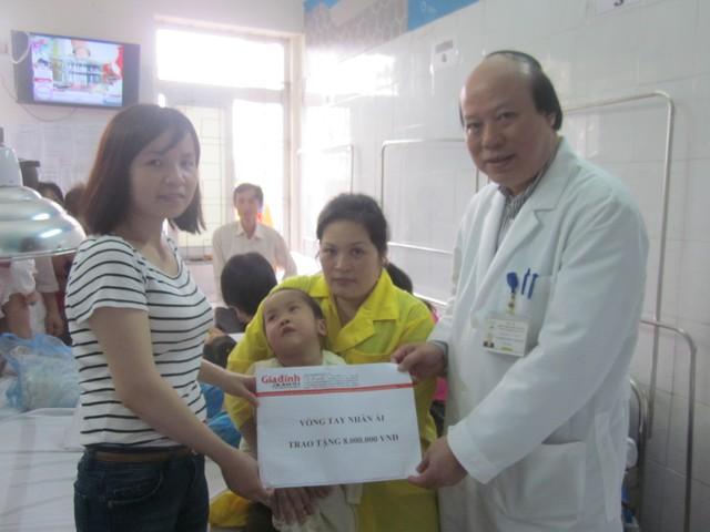 PV Phương Thuận - đại diện Quỹ vòng tay nhân ái (trái) cùng PGS. TS Nghiêm Hữu Thành - Giám đốc BV Châm cứu TƯ trao quà bạn đọc hảo tâm giúp đỡ bé Đức Thắng