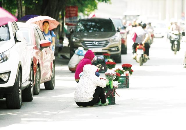 Ngồi bán hoa dưới lòng đường Nguyễn Trãi có mật độ giao thông rất đông.
