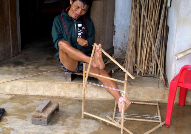 Anh Cầm tự đan lồng chim bằng đôi chân để kiếm sống. Ảnh: Thái Bình