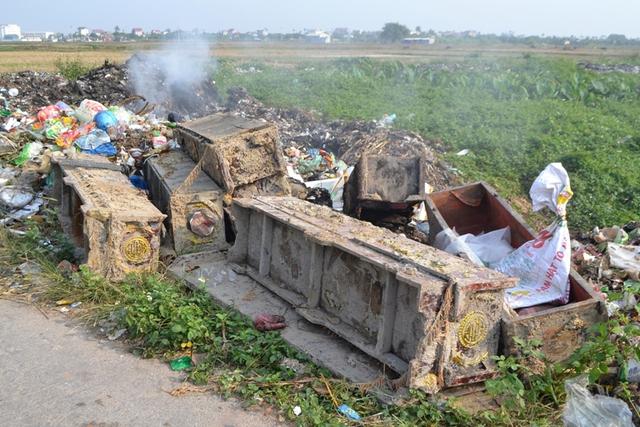 Hàng chục chiếc quan tài vất ngổn ngang cạnh bãi rác. Ảnh: Đ.Tuỳ