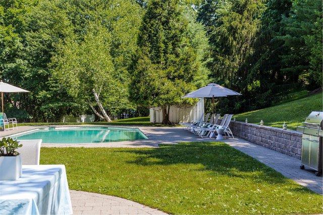 Bên ngoài ngôi nhà là một bể bơi được bao quanh bởi cây xanh thích hợp cho những lúc thư giãn.