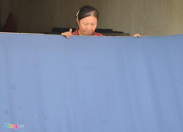 Một người phụ nữ gồng mình đưa những tấm biển quảng cáo cỡ lớn bằng sắt ra ngoài tại quán karaoke 16 Nguyễn Khang.