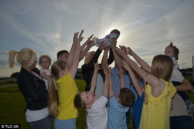 11 đứa con lớn của vợ chồng chị Mandy vui đùa với cô em út mới sinh.