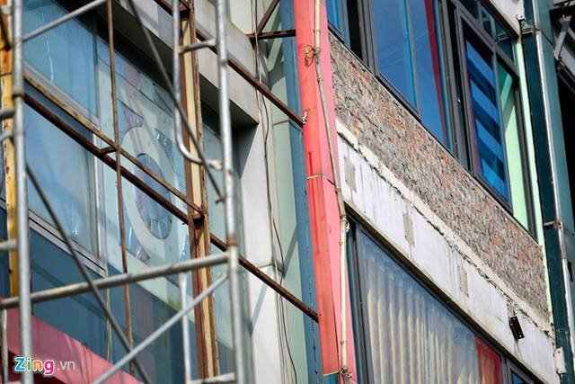 Sau lớp biển quảng cáo là lớp kính dày đặc của một quán karaoke trên đường Trần Duy Hưng.