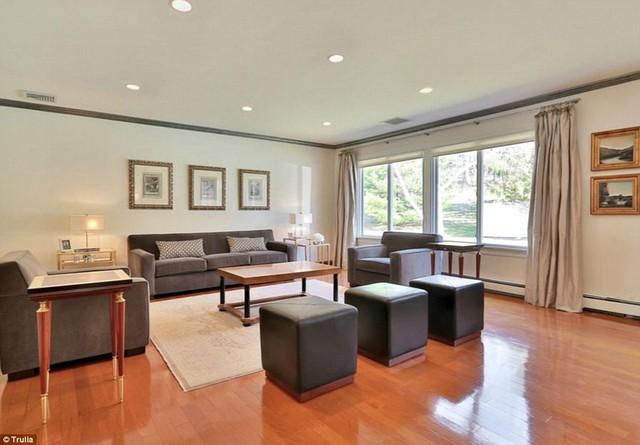 Phòng khách giản đơn với nội thất da lộn màu xám và sàn gỗ ấm áp.