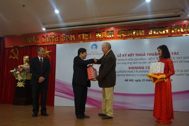 Ông Michael Evans tặng quà cho Thứ trưởng Bộ Y tế Nguyễn Viết Tiến và Phó Tổng cục trưởng phụ trách Tổng cục DS-KHHGĐ Nguyễn Văn Tân. Ảnh: N.Mai