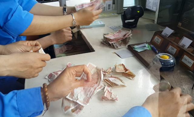 Nhân viên trạm thu phí phải tăng cường thêm người để đếm tiền lẻ người dân mua vé.