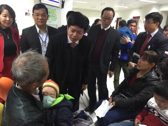 Ông Nguyễn Trọng Khoa - Phó Cục trưởng Cục Quản lý Khám, chữa bệnh (Bộ Y tế) hỏi thăm tình hình sức khoẻ người nhà một bệnh nhi chờ khám tại BV Nhi Trung ương.