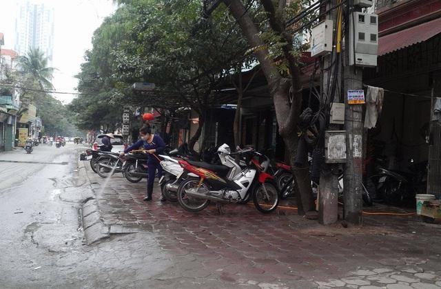 Vỉa hè còn được sử dụng làm nơi rửa xe máy trên đường 19/5 (quận Hà Đông). Ảnh:H.Phương