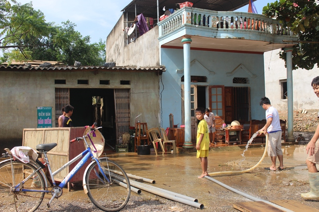 Nhiều hộ dân trở về sau lũ, lo dọn dẹp, lau chùi bùn đất.     ảnh: T.G