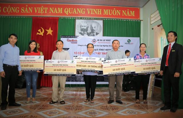 Nhà báo Nguyễn Mạnh Cường (ngoài cùng, bên trái) - Trưởng đại diện phía Nam báo Gia đình và Xã hội cùng nhà tài trợ trao quà cho bà con.