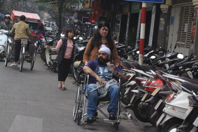 Xe máy đẩy người đi bộ xuống lòng đường ở phố Cầu Gỗ.