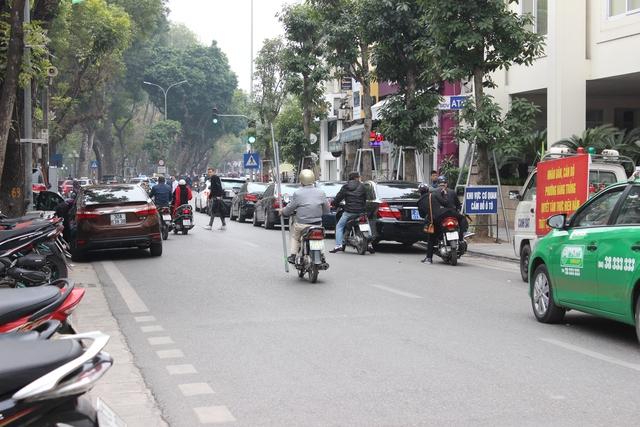 Phương tiện giao thông đậu kín lòng đường, gây khó khăn cho người đi lại. Ảnh:Đ.Vân