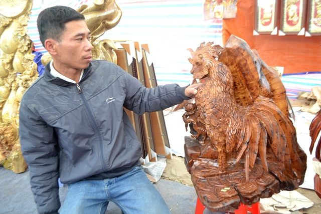 Những chú thần Kê làm bằng gỗ gụ hương đang hút khách mua. Ảnh: Đ.Tuỳ