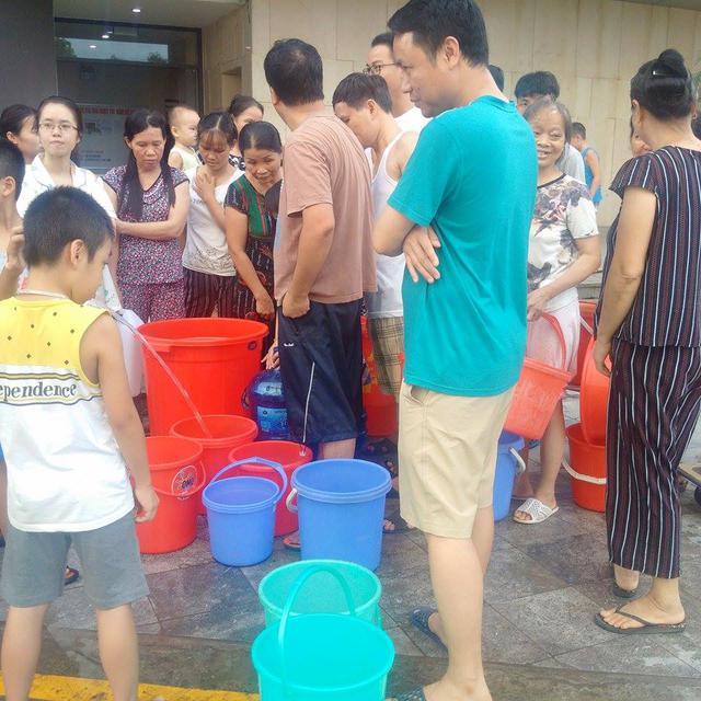 Cư dân HUD3 xếp hàng lấy nước tử bể nước cứu hỏa. Ảnh: H.Phương
