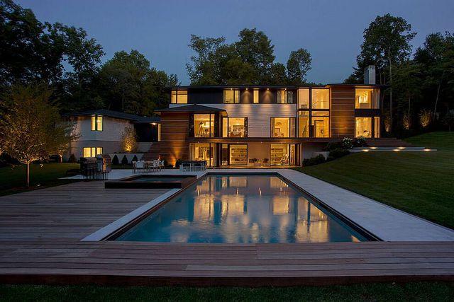 Phía sau nhà là khoảng diện tích đẹp ấn tượng với thảm cỏ xanh, bể bơi và sàn gỗ làm nơi vui chơi, tổ chức tiệc tùng.