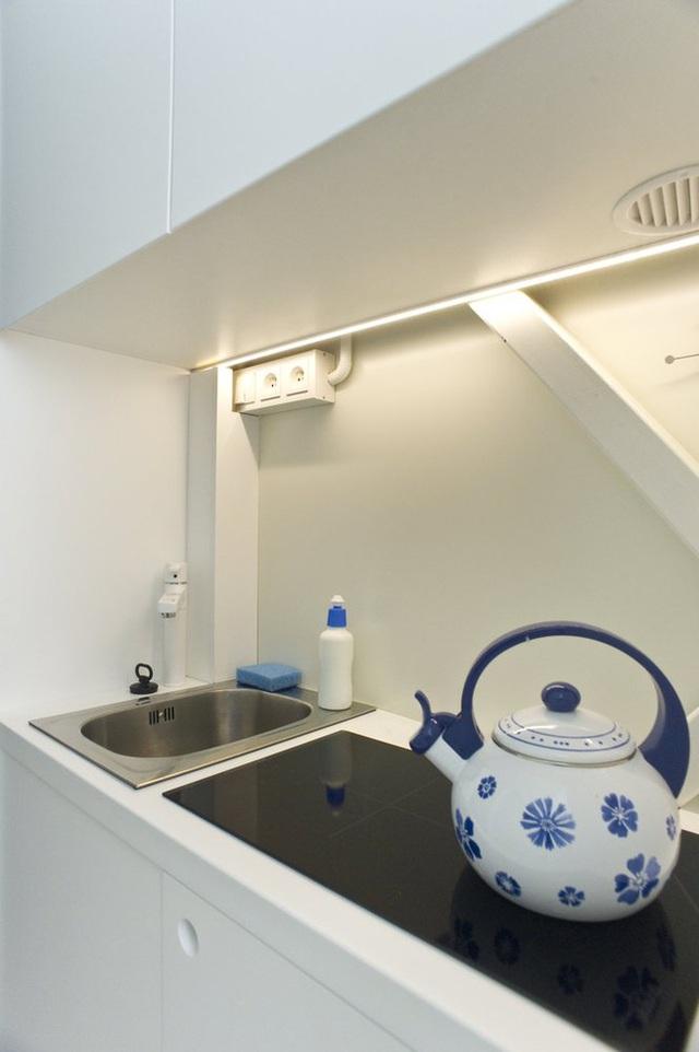 Bếp siêu nhỏ với một bếp, một bồn rửa năm tích hợp trong khối tủ lưu trữ.