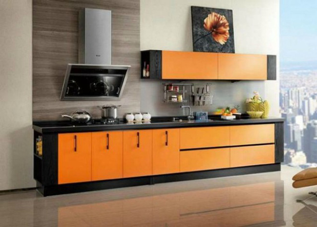 Nếu sợ hãi với những vết dầu mỡ cứng đầu, bạn có thể chọn thiết kế tủ bếp Acrylic, loại vật liệu dễ dàng lau chùi và phổ biến của các loại tủ kệ ở những căn hộ cao cấp. Sắc cam phối hợp với màu đen tạo nên cái nhìn mạnh mẽ, nổi bật.