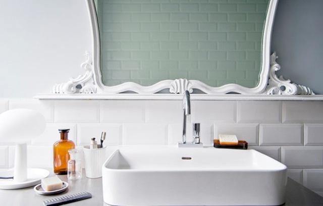 Viền gương màu trắng với đường nét cổ điển, tạo điểm nhấn dịu dàng trên bức tường ốp gạch trắng.