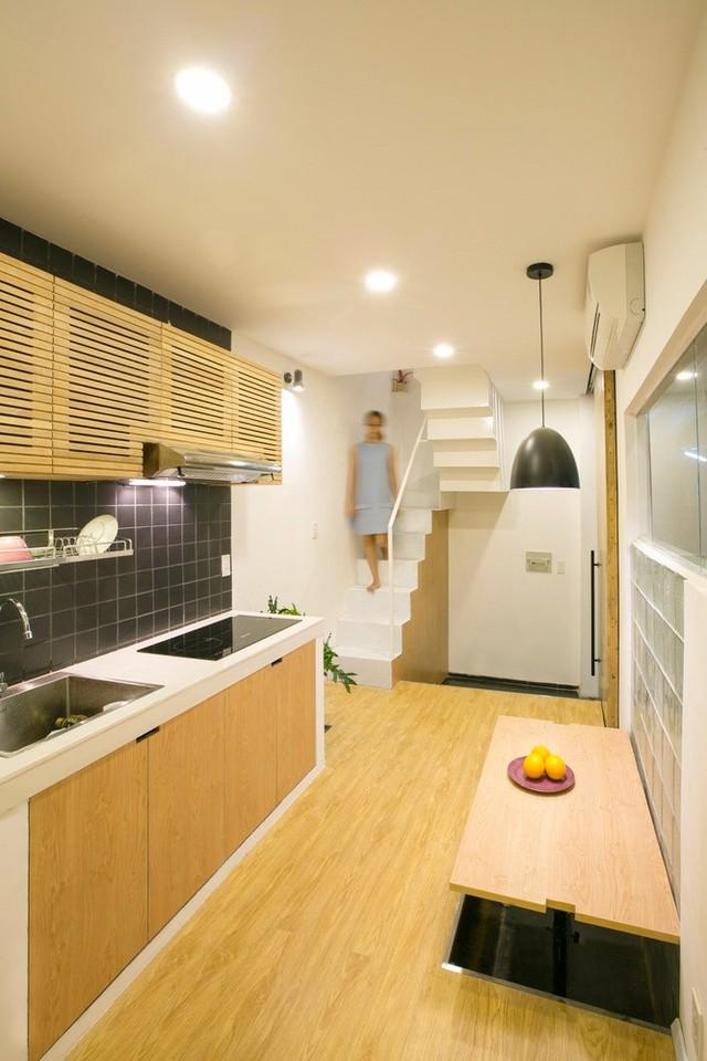 Bức tường gần bàn ăn chính được thiết kế với chi tiết kính mờ đóng vai trò làm cửa sổ lấy sáng mà vẫn đảm bảo tách biệt căn phòng với không gian bên ngoài.