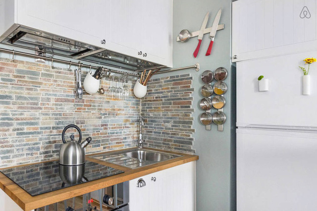 Khu vực nấu nướng được bố trí sát góc tường bên trong nhưng không vì thế mà chật chội, bức bối. Phần tường gần bếp nấu và bồn rửa được ốp đá tự nhiên tạo điểm nhấn đặc biệt.