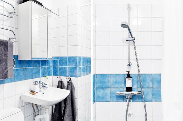Phòng tắm thoáng mát với điểm nhấn từ màu xanh trên tường.