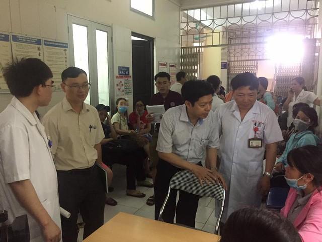 ThS Nguyễn Trọng Khoa (thứ 3 từ trái sang) thăm hỏi bệnh nhân đang đến chờ khám ở Bệnh viện Bệnh Nhiệt đới Trung ương.
