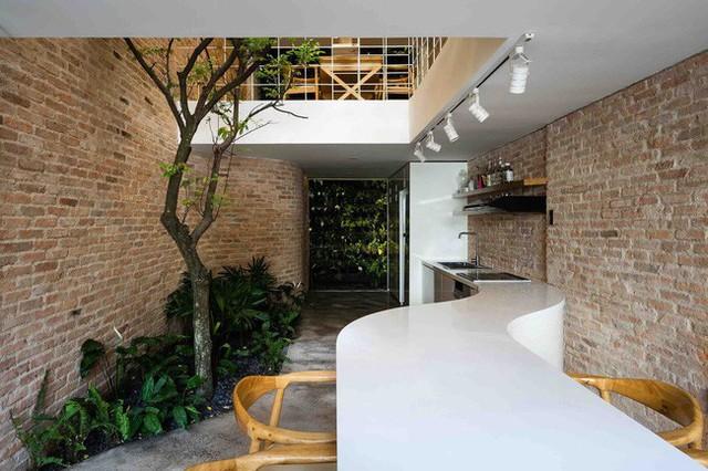 Tủ bếp dài kết hợp bàn ăn được sơn trắng uốn lượn tạo sự mềm mại uyển chuyển.
