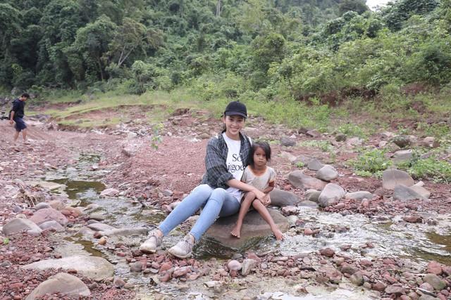 Người đẹp chụp ảnh với một bé gái địa phương
