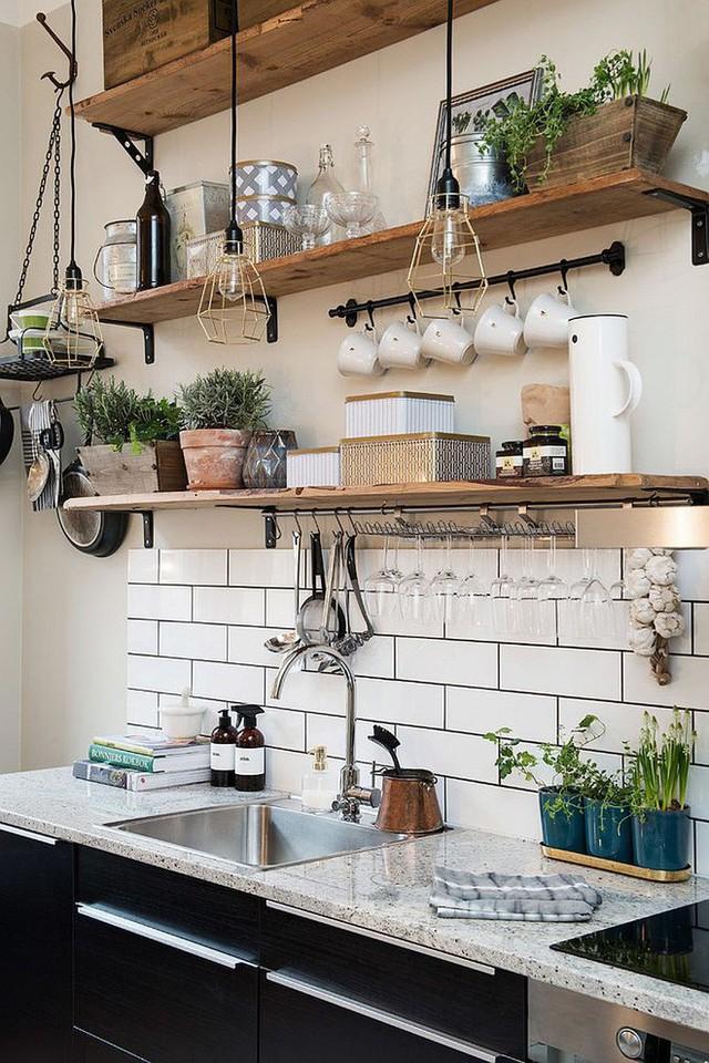 Căn bếp với màu trắng mang phong cách Scandinavian càng đẹp hơn khi có sự hiện diện của kệ gỗ nổi bật. thêm chút dịu dàng từ cây cỏ, chút đơn giản từ cách sắp xếp là đủ để không gian đẹp hơn.