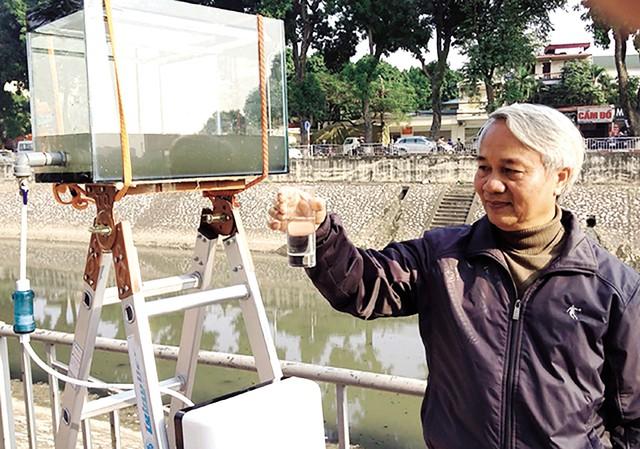 """PGS.TS Trần Hồng Côn bên máy lọc nước """"biến"""" nước sông Tô Lịch thành nước uống. Ảnh: ĐH Quốc gia Hà Nội"""