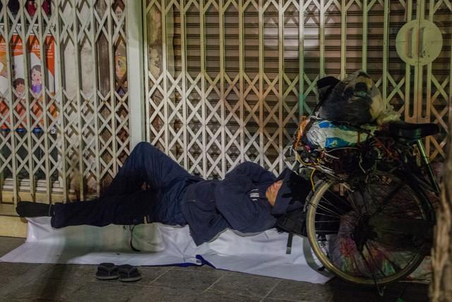 Một người vô gia cư đang nằm ngủ co ro trên phố Tràng Thi trong đêm đông giá rét đến tê người.