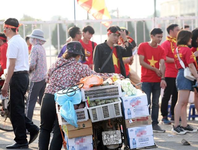 Một chủ tiệm hàng bán đồ ăn vặt nhanh chân chở hàng đến quảng trường bán.