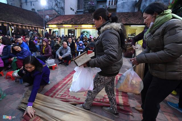 Hơn 17h, hàng nghìn người đổ về đây mang theo ghế, chiếu, báo... để chiếm chỗ ngồi trong sân chùa.