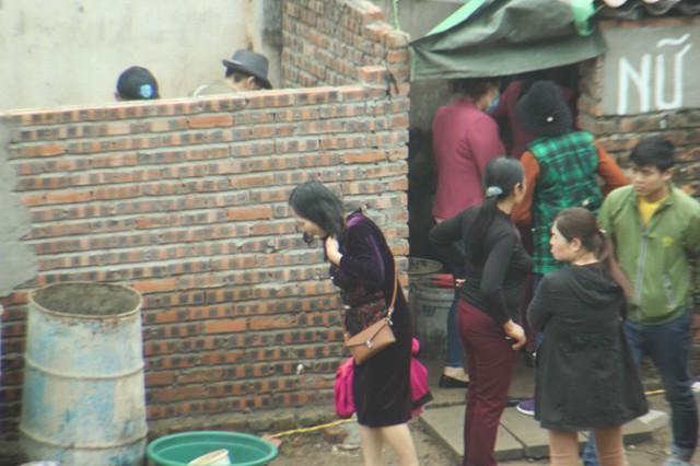 Một người phụ nữ vừa trong nhà vệ sinh ra, có vẻ người phụ nữ này không hài lòng về chất lượng của nhà vệ sinh dựng tạm. Ảnh: Dân Việt