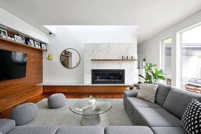 Phòng khách hiện đại với lò sưởi bằng đá cẩm thạch và tường bằng gỗ.